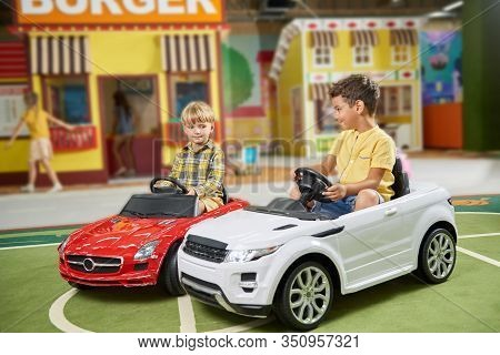 Two Preschool Boys Ride On Toy Car In Playground. Kids Riding Small Car In Amusement Park. Happy Kid