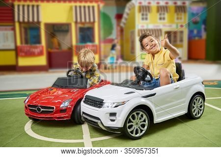 Happy Little Boys Having Fun At Entertainment Center. Kids Driving Toy Car In Game Center. Interior