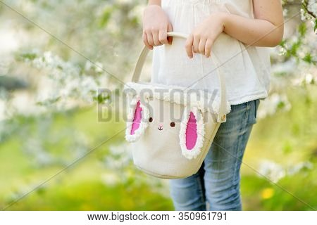 Close-up Of Little Girls Hands Holding Cute Easter Basket In Blooming Cherry Garden On Beautiful Spr