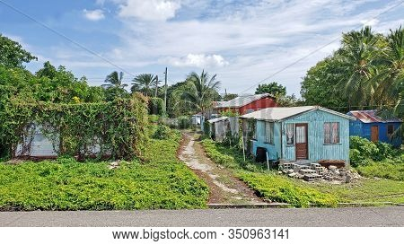 Three Colorful Typical Homes In Antigua Barbuda Lesser Antilles, West Indies, Caribbean.