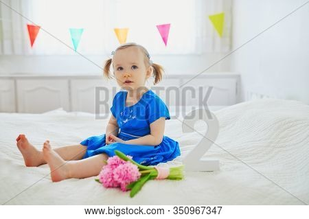 Adorable Toddler Girl In Blue Dress Sitting On Bed With Pink Hyacinths And White Wooden Number Two.