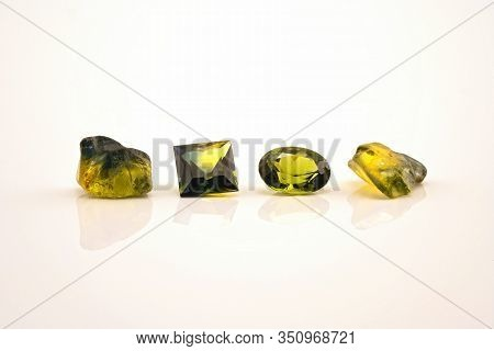 Two Facet Cut Yellow Green Sapphire With Two Uncut Natural Sapphires Of A Similar Colour, Isolated O