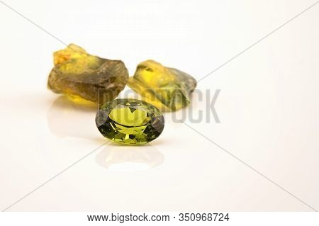 One Oblong Facet Cut Yellow Green Sapphire With Two Uncut Natural Sapphires Of A Similar Colour, Iso