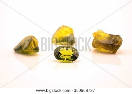 One Oblong Facet Cut Yellow Green Sapphire With Three Uncut Natural Sapphires Of A Similar Colour, I