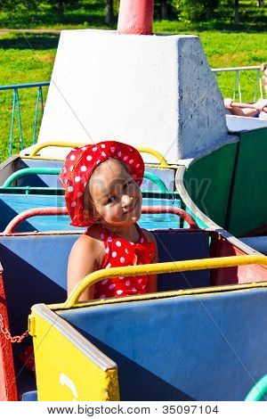 A Little Girl Riding On A Children's Train
