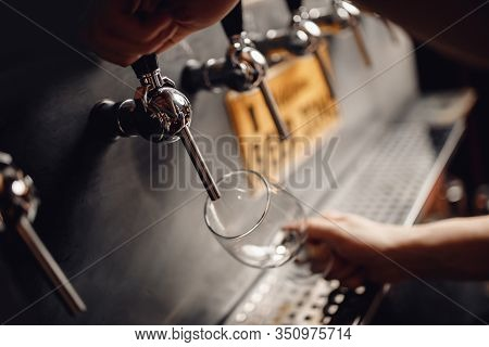 Barman Pours Light Alcoholic Cider Of Keg Tap Into Glass. Dark Background