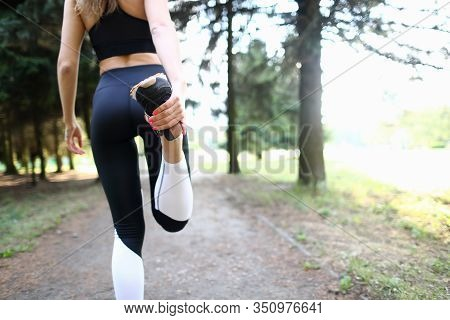 Kneading, Warming Up Body Muscles Before Jogging. Girl In Tracksuit Holds Her Foot And Bends Leg At