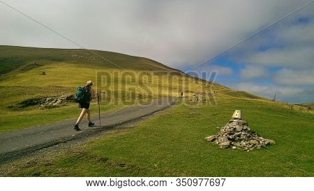 Pilgrim Woman Walking In The Mountains Of The Pyrenees, On The Border Between France And Spain. Ronc