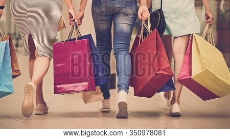 Back View Legs Of Three Stylish Women With Paperbags After Shopping