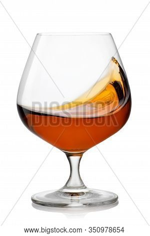 Splash Of Brandy In Snifter Glass Isolated On White Background