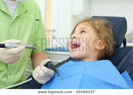 Dentist hands hold saliva suction and grinding drill, happy girl opens her mouth in dental clinic.
