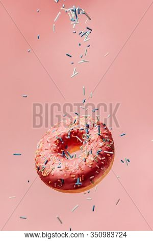 Big Tasty Donut With Pink Icing Hanging In The Air On A Pink Background. A Confectionery Decorations
