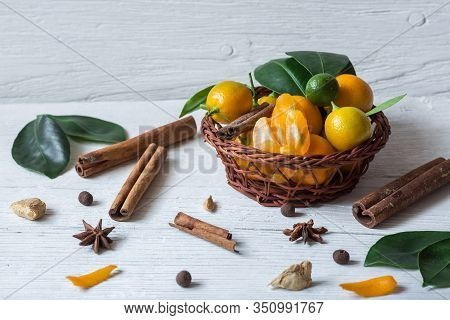 Christmas Composition On Old White Wood. Still Life With Calamondines In Basket, Cinnamon Sticks, An