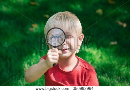 Boy With Magnifying Glass Outdoors. Investigation Discovery Vision