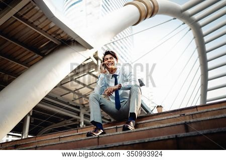 Happy Young Businessman Sitting On Staircase And Using Smartphone. Urban Lifestyle. Low Angle View.
