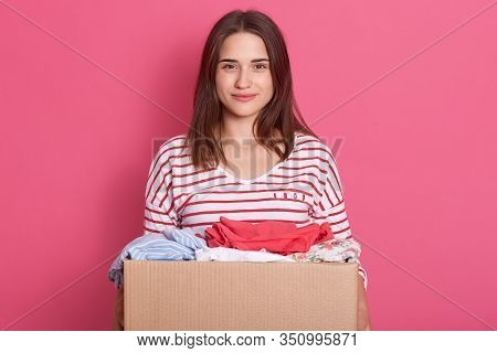 Horizontal Shot Of Positive Attractive Cute Volunteer Looking Directly At Camera, Holding Paper Box