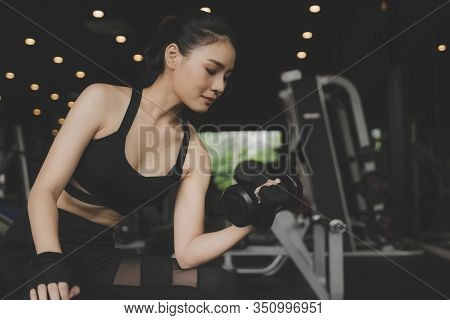 Athletic Young Pretty Asian Slim Body Woman In Black Sport Bra Exercise With Dumbbell In Fitness Gym