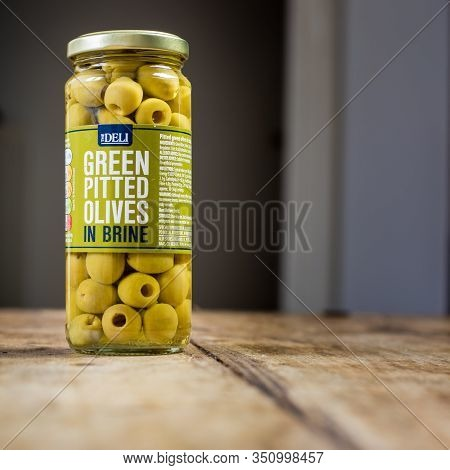 Perth, Scotland - 11 November 2019: Green Pitted Olives In Brine Isolated On Vintage Wooden Table