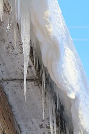 Large Icicles Hanging From Roof Of Brick House On Blue Sky Background. Bottom View. Stock Photo With