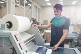 Serious young printing specialist with beard operating printing press while printing test page at factory
