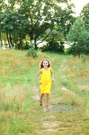Cute Little Girl Is Running On The Road At Countryside On A Warm Summer Sunset.