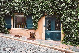 Beautiful Street Shop In Germany, Europe. Lush Green On Facade Of Building, Cobblestone Walkway In F