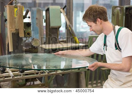 glazier deburrs a glass on grinding machine in workshop poster