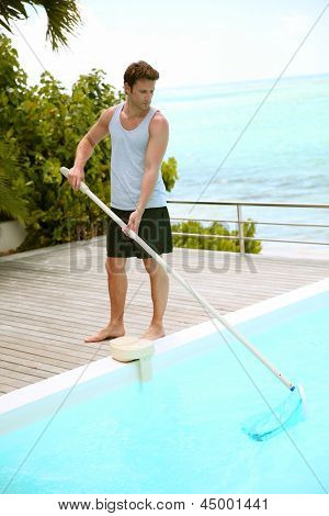 Swimming-pool service man cleaning water