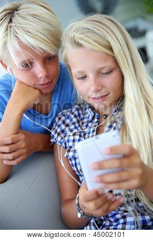 Teenagers using smartphone with earphones