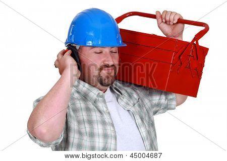 Tradesman pretending to listen to music
