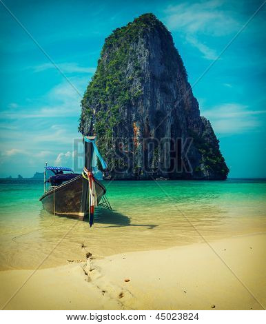 Long tail boat on tropical beach with limestone rock, Krabi, Thailand. Vintage style, cross process