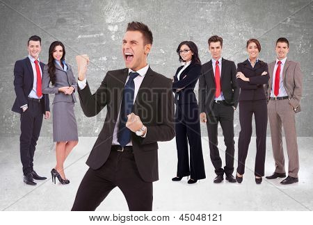 young business man leader screaming of joy in front of his successful team