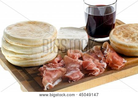 cutting board with small round flat bread, ham, cheese and glass of red wine, typical dish of Emilia-Romagna poster