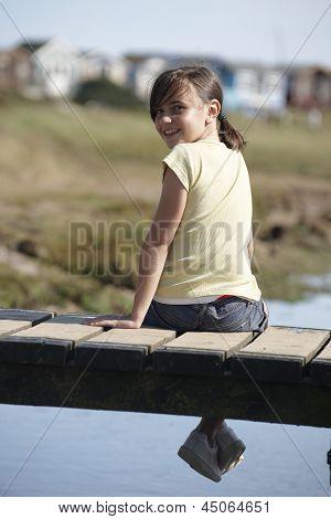 Girl Sitting On Bridge Smiling At Camera