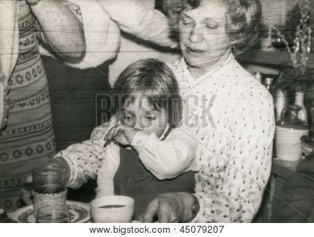 Vintage photo of grandmother with her granddaughter during a family party, early eighties