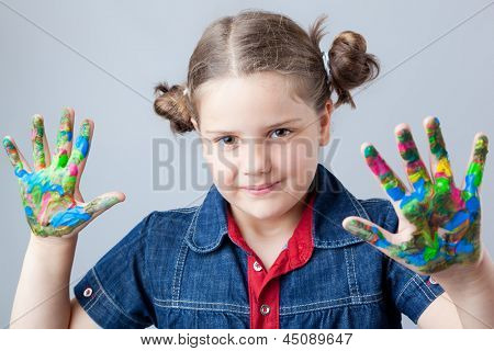 Beautiful little girl showing painted hands over grey background