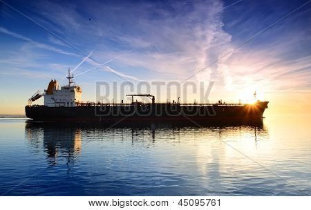 Cargo ship sailing away against colorful sunset