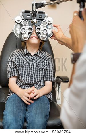 Preadolescent boy undergoing eye examination with phoropter in store