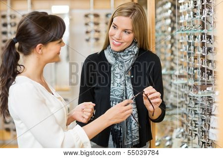 Young salesgirl and female customer holding glasses while looking at each other in shop