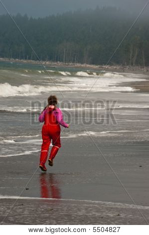 Young Girl In Red Rain Clothes On Ocean Beach, Washngton, Usa