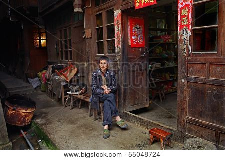 Asian Trader In Green Sneakers, Sits Near A Village Shop.
