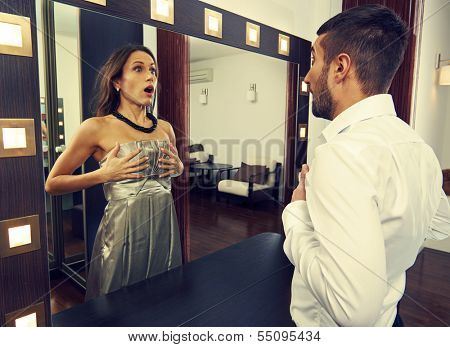 frightened man looking at woman in the mirror