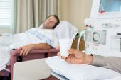 Male cancer patient's hand holding glass of crushed ice in dialysis room at hospital poster