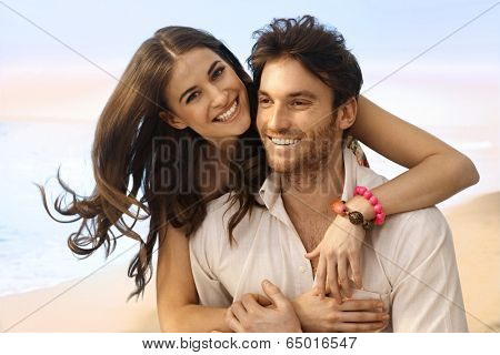 Portrait of happy casual caucasian married couple at the beach. Handsome man, attractive young woman, smiling, looking at camera, embracing.