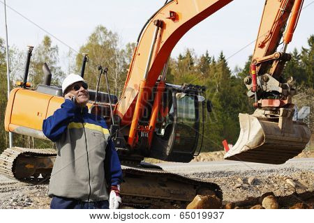 construction worker talking in phone, large bulldozer, digger in background
