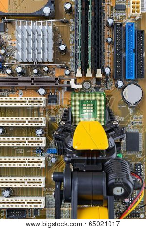Robotic arm installing a computer chip on a motherboard.