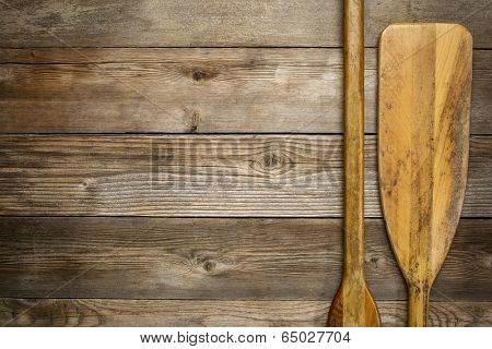 blade and grip of wooden canoe paddle against rustic wood background with a copy space