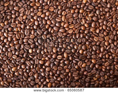 Numerous coffee beans which have been scattered all over the surface