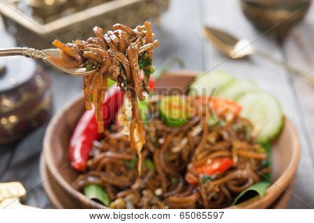 Delicious Asian spicy fried noodles, ready to serve on dining table.