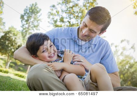 Loving Young Father Tickling Son in the Park.